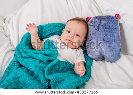 Baby is wrapped in a blanket . side cushion in the shape of a teddy bear - stock photo