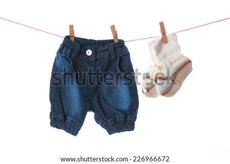 Baby jeans and shoes hanging on the clothesline over the white background. - stock photo