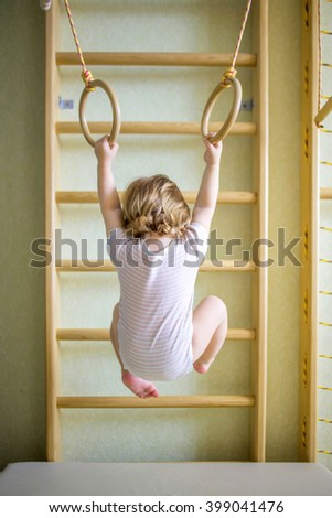 Baby kid playing sports on the gymnastic rings in the gym class. Back view.