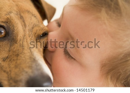 Baby kissing dog - stock photo