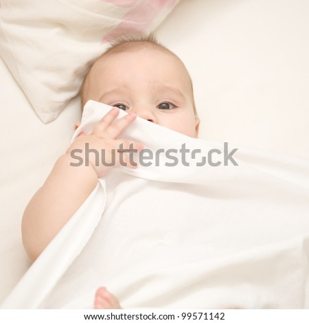 Baby laughing and playing in bed with a sheet - stock photo