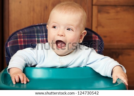 baby laughing, sitting on a chair