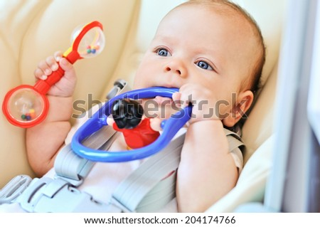 baby laying in bouncer chair with toys
