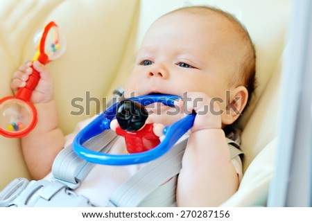 baby laying in bouncer chair with toys - stock photo