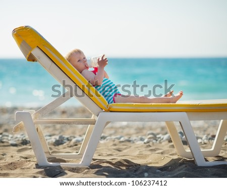 Baby laying on sunbed and drinking water - stock photo