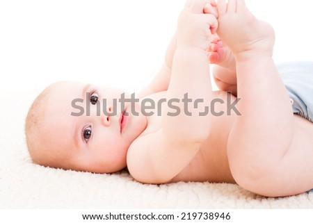 baby laying on white sheets in bed - selective focus on baby face - stock photo