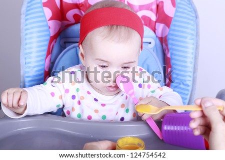 Baby learn to eat  with spoon - stock photo