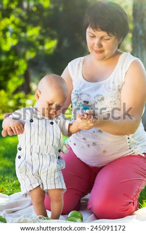 Baby learning to walk outdoors. Happy mum and her child playing in park together. Outdoor portrait of happy family