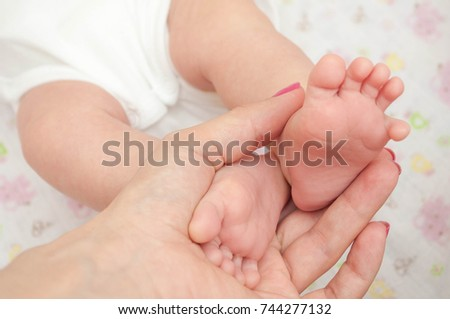 baby legs in hand. Baby's legs.  Little feet of the newborn. Baby's leg in Mom's hand