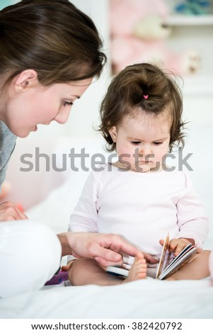 Baby little girl looking at book  while mom  reading the interesting story and showing the pictures .Shallow doff