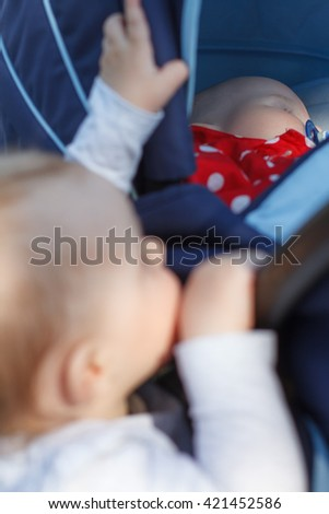 baby looking at the sleeping newborn - stock photo
