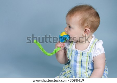Baby looking to left and chewing on flower - stock photo