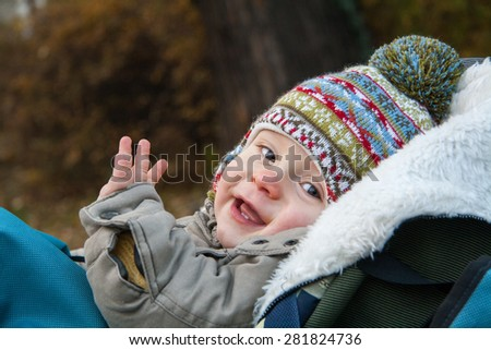 baby lying in baby carriage, open eyes, in warm hat and jacket, winter or autumn time. Portrait. - stock photo