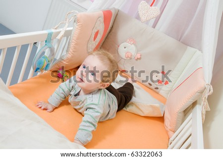 baby lying in the latticed bedsted and plays - stock photo
