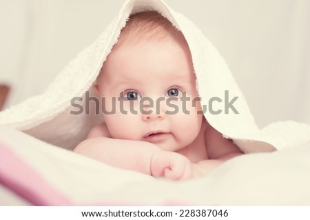 baby lying on a bed under towel - stock photo