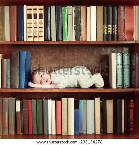 baby lying on book shelf in bookcase - stock photo