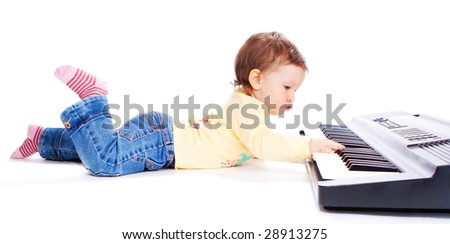 Baby lying on floor and playing synthesizer - stock photo