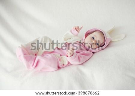 Baby lying on white blanket in Bunny costume. - stock photo
