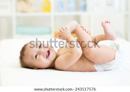 baby lying on white sheet and holding his legs - stock photo