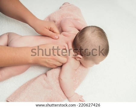 Baby massage doctor massage small caucasian baby boy back - stock photo