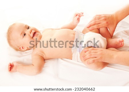 Baby massage. Mother massaging kid legs and feet, baby laughing. Isolated on white background - stock photo