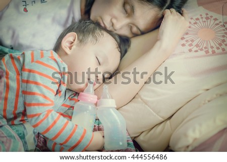 Baby milk bottle and water bottle holding by asian baby boy. Asian baby boy sleeping in mother arm  - stock photo