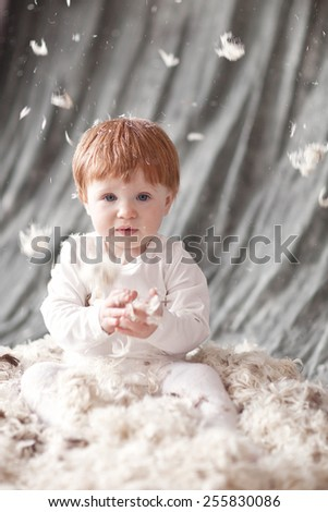 Baby Newborn with feather. Child Sitting at feathers pile and cath feathers.