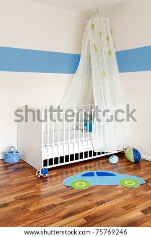 Baby nursery with bed and blue colored stripe on wall - stock photo