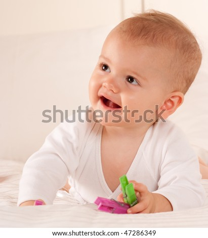 Baby on a bed playing with colourful plastic pegs