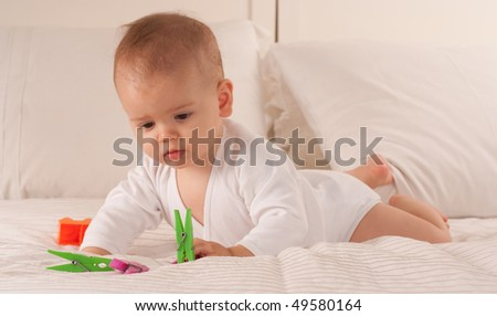 Baby on a bed playing with colourful plastic pegs - stock photo