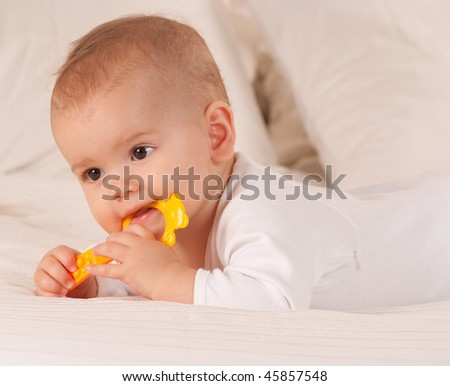Baby on a bed playing with plastic yellow toy