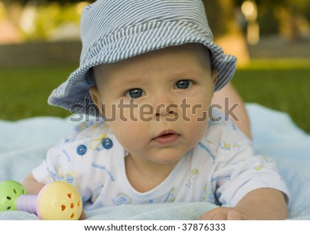 Baby on coverlet  in hat from sun - stock photo
