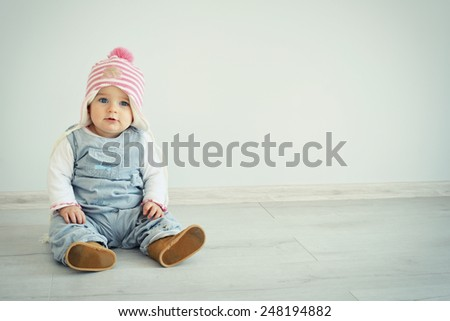 Baby on floor. A cute little girl is looking into the camera and is wearing a pink knitted hat. Blue eyes kid. Parenting or love concept. - stock photo
