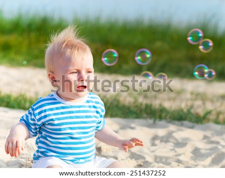 Baby on the beach playing with soap bubbles. Summer