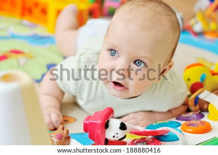 baby on the carpet with toys - stock photo