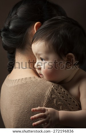 baby on the mother's shoulder. Photo in low key - stock photo