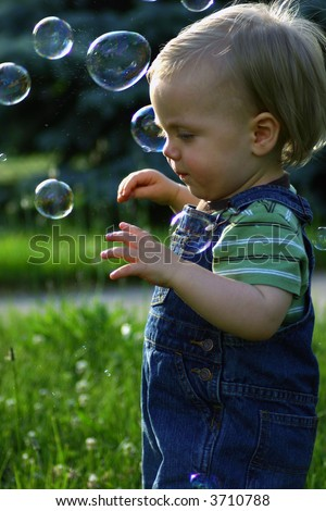 Baby, one year old playing with bubbles, profile - stock photo