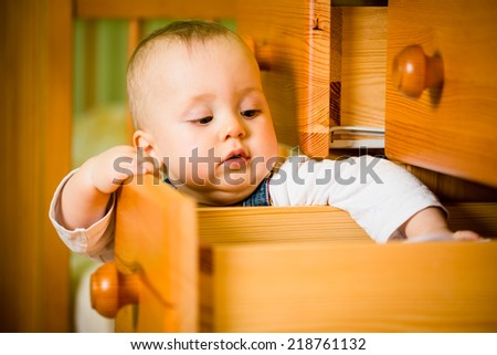 Baby opening drawer with clothes on wooden furniture - home interior - stock photo