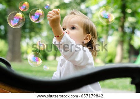 baby outdoors or park playing with soap bubbles