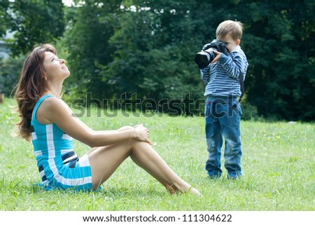 Baby  photographer takes photo the girl in park - stock photo