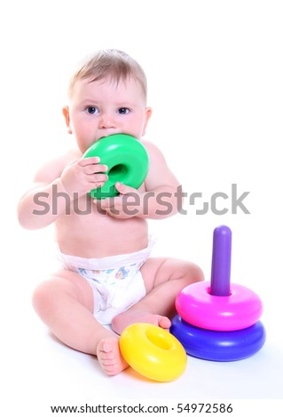 Baby play with tower from colorful discs isolated on white