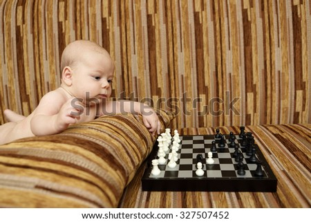 Baby playing chess on the sofa at home - stock photo