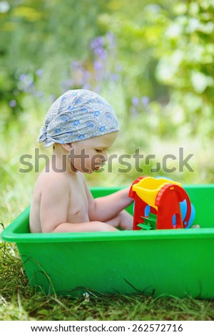 Baby playing in a bathtub in the garden - stock photo