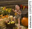 Baby playing in a wooden shed with with apples and pumpkins - stock photo