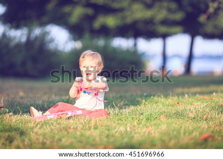 Baby playing on Outdoors. Computer mouse. - stock photo