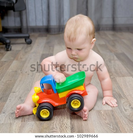 baby playing with a toy car - stock photo