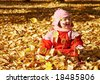 Baby playing with autumn leaves - stock photo