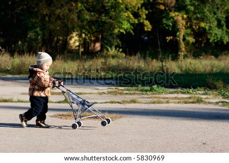 Baby playing with carriage - stock photo