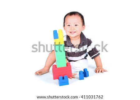 Baby playing with colorful blocks and sitting in studio, isolated on white background - stock photo