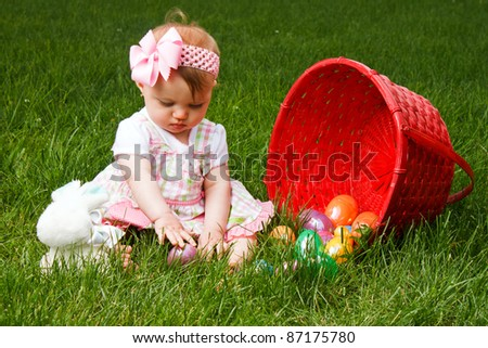 Baby playing with Easter eggs while sitting beside a spilled red basket - stock photo